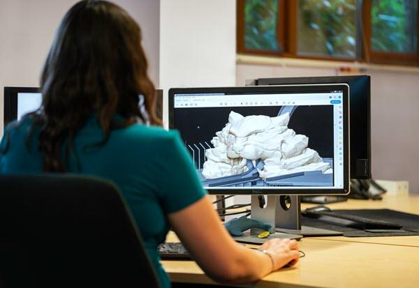 Imagen de una chica delante de una pantalla comprobando la ergonomía de un monitor de ordenador